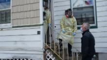 Storzillo discusses a patient with a Paterson fire supervisor before entering a residence.
