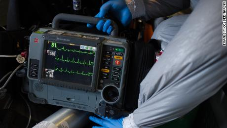 EMT Besselman checks a monitor for a suspected Covid-19 patient.
