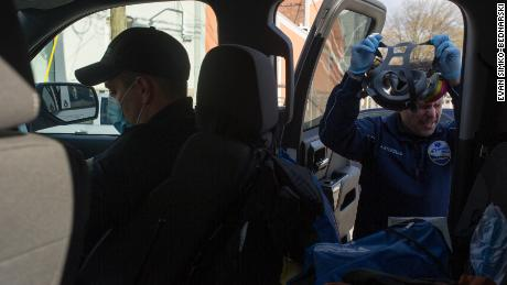 Incorvaia, in front seat, dons a surgical mask; Storzillo removes his respirator.