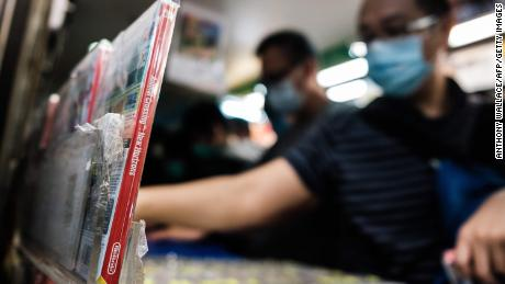 A copy of Nintendo computer game Animal Crossing: New Horizons (L) is displayed in a shopping mall as customers browse other games while wearing face masks, as a precautionary measure against the COVID-19 coronavirus, in Hong Kong on April 10, 2020. (Photo by Anthony Wallace/AFP/Getty Images)