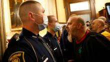 Protesters face police outside the doors to the Michigan House of Representatives.