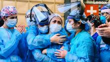 Medical workers embrace outside Lenox Health Greenwich Village on Thursday as New Yorkers applaud medical staff and essential workers on the front lines of the coronavirus pandemic.