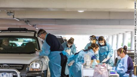 Medical practioners conducting tests for Covid-19 at a drive-thru testing facility in a parking lot on April 30 in Melbourne, Australia.