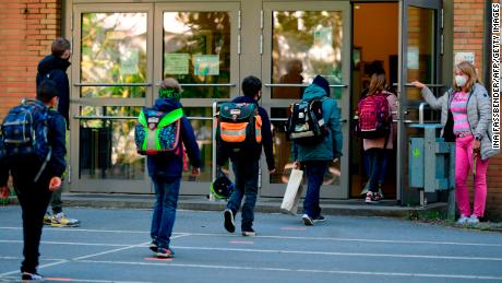Children respect social distancing rules as they enter the Petri primary school in Dortmund, western Germany, on Thursday, as the school reopens for some pupils.