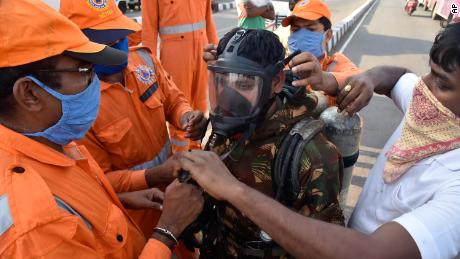 A member of India's National Disaster Response Force (NDRF) is fitted with protective gear before he enters the area affected by the leak.