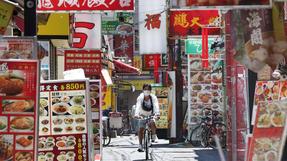 A man wearing a face mask cycles through Chinatown in Yokohama, Giappone, a Maggio 8. Prime Minister Shinzo Abe announced that Japan will extend its state of emergency until the end of May.