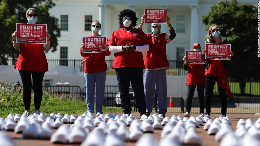 During a protest in Washington on May 7, members of National Nurses United stand among empty shoes that they say represent nurses who have died from Covid-19.