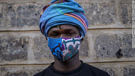 """Kenyan fashion designer of """"Lookslikeavido"""", David Avido, poses for a portrait at his studio in Kibera, Nairobi, with a mask he created to hand out to people for free."""