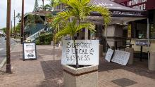 """Support Local Business"" signs are posted along Front Street in Lahaina, Hawaii, on Friday."