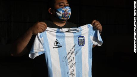 A man holds a replica of Argentina's football team jersey used during the final of the 1986 World Cup and signed by Diego Maradona.