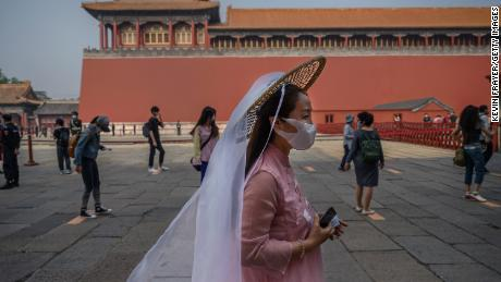 Chinese tourists wear protective masks as they line up to enter the Forbidden City.