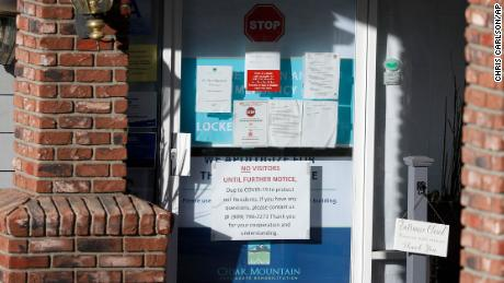 Warning notices were posted on a door at an entrance to the Cedar Mountain Post Acute nursing facility in Yucaipa, Calif. There have been 21 resident deaths there -- the highest number of Covid-19 deaths in any facility in San Bernardino County.