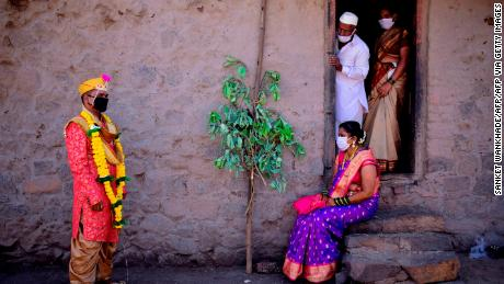 Groom Vitthal Koditkar, left, of Hirpodi village speaks with his bride Vrushali Renuse, right, of Pabe village and family members after their wedding during a government-imposed nationwide lockdown at Pabe village in Pune district in Maharashtra, India.