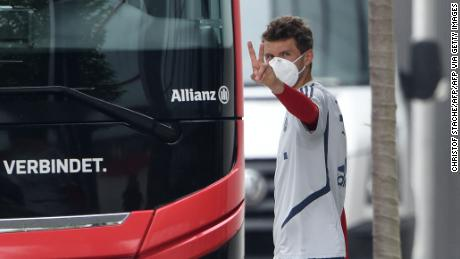 Bayern Munich striker Thomas Mueller wears a face mask as he leaves a training session.