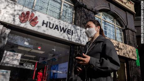 Una mujer con una máscara facial en medio de preocupaciones por el coronavirus Covid-19 camina sosteniendo su teléfono inteligente frente a una tienda Huawei (L) en una calle en Beijing el 22 de abril de 2020.