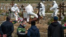 Los cavadores de tumbas entierran a una víctima de COVID-19 mientras familiares y amigos se encuentran a una distancia segura, en un cementerio en Kolpino, a las afueras de San Petersburgo, el viernes.