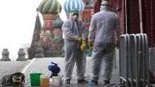 Personas con equipo de protección desinfectando la Plaza Roja en Moscú.