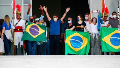 Bolsonaro waves to supporters during a rally in Brasilia on Sunday.