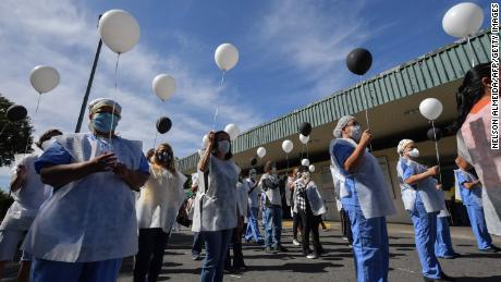 Health professionals hold balloons as they honour colleagues who have died of the coronavirus, outside Sao Paulo University Hospital.