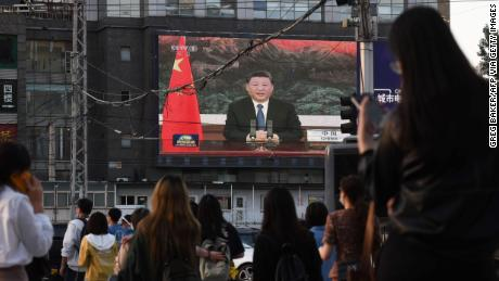 A news program shows Chinese President Xi Jinping speaking via video link to the World Health Assembly on a giant screen beside a street in Beijing on May 18.