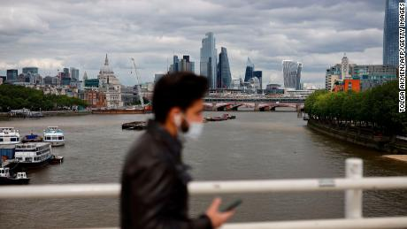 A pedestrian walks on Waterloo Bridge to cross the River Thames, backdropped by the skyscrapers and office buildings of the City of London, on May 13, 2020, as people start to return to work after COVID-19 lockdown restrictions were eased. - Britain's economy shrank two percent in the first three months of the year, rocked by the fallout from the coronavirus pandemic, official data showed Wednesday, with analysts predicting even worse to come. (Photo by Tolga Akmen/AFP/Getty Images)
