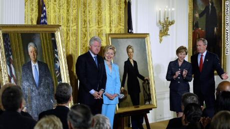 Former President Bill Clinton and former first lady Hillary Clinton stand by their offical White House portraits during the unveiling event hosted by then-President George W. Bush and first lady Laura Bush in June 2004 at the White House.