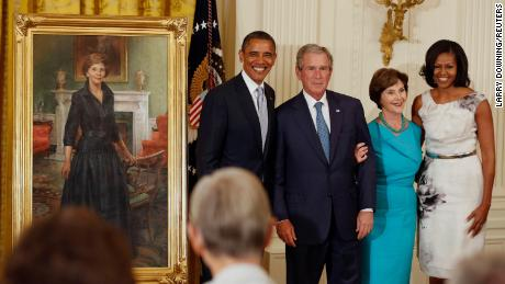 Former President George W. Bush stands next to then-President Barack Obama while former first lady Laura Bush stands next to then-first lady Michelle Obama during the unveiling of their official White House portraits in the East Room of the White House in May 2012.