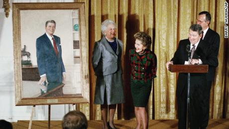 Former President Ronald Reagan and former first lady Nancy Reagan take a peek at a portrait of the former president along with then-President George H.W. Bush and then-first lady Barbara Bush during an unveiling ceremony at the White House in November 1989.