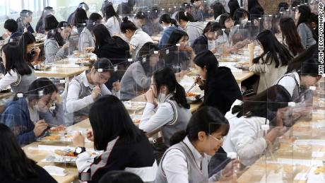 Senior students eat lunch at tables equipped with plastic barriers to prevent possible spread of coronavirus in the cafeteria at Jeonmin High School in Daejeon, South Korea, Wednesday, May 20, 2020.