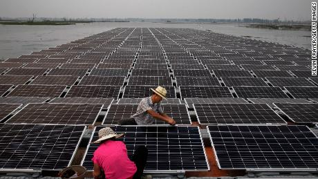 HUAINAN, CHINA - JUNE 12: Chinese workers prepare  panels that will be part of a large floating solar farm project under construction by the Sungrow Power Supply Company on a lake caused by a collapsed and flooded coal mine on June 12, 2017 in Huainan, Anhui province, China. The floating solar field, billed as the largest in the world, is built on a part of the collapsed Panji No.1 coal mine that flooded over a decade ago due to over-mining, a common occurence in deep-well mining in China's coal heartland. When finished, the solar farm will be made up of more than 166,000 solar panels which convert sunlight to energy, and the site could potentially produce enough energy to power a city in Anhui province, regarded as one of the country's coal centers. Local officials say they are planning more projects like it, marking a significant shift in an area where long-term intensive coal mining has led to large areas of subsidence and environmental degradation. However, the energy transition has its challenges, primarily competitive pressure from the deeply-established coal industry that has at times led to delays in connecting solar projects to the state grid. Chinaas government says it will spend over US $360 billion on clean energy projects by 2020 to help shift the country away from a dependence on fossil fuels, and earlier this year, Beijing canceled plans to build more than 100 coal-fired plants in a bid to ease overcapacity and limit carbon emissions. Already, China is the leading producer of solar energy, but it also remains the planetas top emitter of greenhouse gases and accounts for about half of the worldas total coal consumption. (Photo by Kevin Frayer/Getty Images)