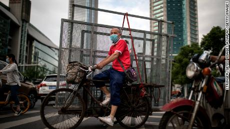 A man wearing a face mask ride tricycles to transport iron nets in Wuhan on May 11.