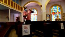 A man helps clean and sanitize pews following an in-person Mass at Christ the King Catholic Church in San Antonio on May 19.
