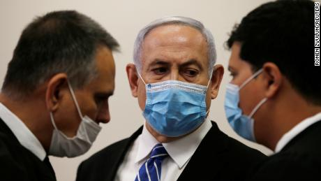 Prime Minister Benjamin Netanyahu stands with lawyers in Jerusalem's District Court on Sunday.