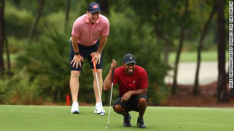Woods and Manning read a putt on the sixth green during The Match: Champions For Charity at Medalist Golf Club.