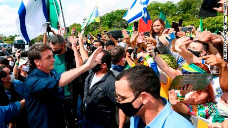 Bolsonaro greets supporters upon arrival at Planalto Palace in Brasilia, on May 24, 2020, amid the COVID-19 coronavirus pandemic.