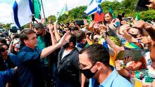 Bolsonaro greets supporters upon arrival at Planalto Palace in Brasilia, on May 24, 2020, amid the COVID-19 coronavirus pandemic.