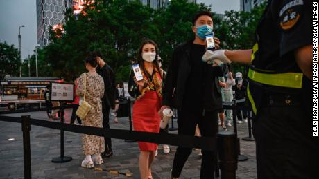 A Chinese man and woman in Beijing show their local health QR codes to a security guard as he checks her temperature before entering a shopping area on May 3.