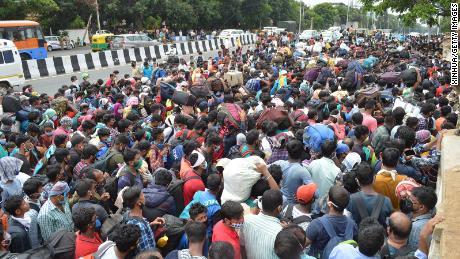 Muncitorii migranți așteaptă să urce pe autobuze în timpul blocării coronavirusului din Bangalore pe 23 mai 2020.