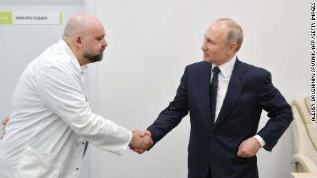 Russian President Vladimir Putin, right, shaking hands with Denis Protsenko, the head of a new hospital treating coronavirus patients in Moscow on March 24.