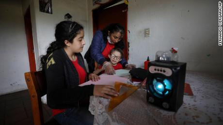 A family listens to an hour-long radio lesson from their home in Funza, Colombia, where they have no internet connection.