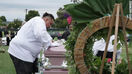 Jesse Macias, Guadalupe Ortiz-Sandoval's son, kisses his mother's coffin as others watch from a distance at Forest Lawn Cypress cemetery in California.