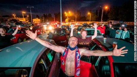Fans cheer as they watch the Czech first division football match between FC Viktoria Plzen and AC Sparta Praha at a drive-in movie theater in Plzen, Czech Republic.