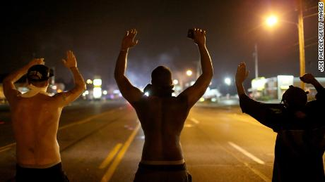 Demonstrators raise their arms as they protest the shooting death of Michael Brown on August 17, 2014 in Ferguson, Missouri.