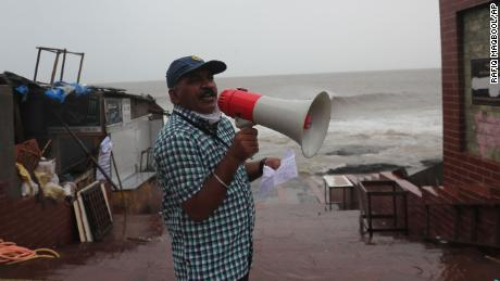 A municipal employee makes a warning announcement by the shore of the Arabian Sea in Mumbai, India, June 3.