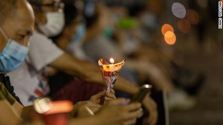 A man holds a candle at Thursday's vigil.