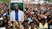 A person holds a portrait of late Adama Traore during a march in Beaumont-sur-Oise, northeast of Paris in 2018 calling for answers in the case.