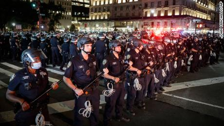 New York Police Department officers stand in formation after arresting multiple protesters marching after curfew on Fifth Avenue in New York.
