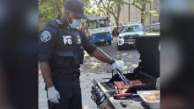 An officer in Camden County, New Jersey, grills hot dogs for one of the department's pop-up neighborhood parties. The city has reformed its police department to focus on de-escalating violence in the community.