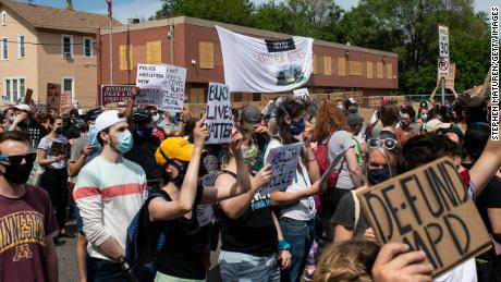 Demonstrators marching to defund the Minneapolis Police Department pause outside the Minneapolis Police and Fire Union Office on June 6.