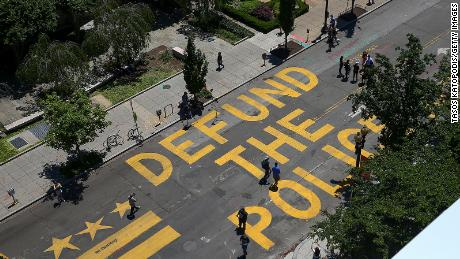 "People walk down 16th street after ""Defund The Police"" was painted on the street near the White House."